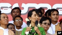 Burma's pro-democracy icon Aung San Suu Kyi talks to supporters at a stadium on her arrival at Pathein, Pathein, Irrawaddy delta, Feb. 7, 2012.