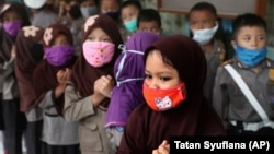 Children wear masks in the wake of the outbreak of a new coronavirus at a kindergarten in Jakarta, Indonesia, Thursday, March 5, 2020. Parents are deciding how to discuss the virus with their children.