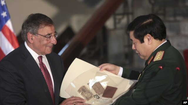U.S. Defense Secretary Leon Panetta, left, gives a Vietnam War memorabilia of a Vietnamese soldier to his counterpart Phung Quang Thanh in Hanoi, Vietnam, June 4, 2012.