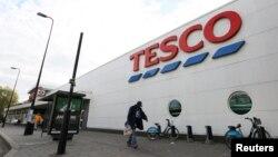 Seorang pria berjalan melewati sebuah toko Tesco di selatan kota London (23/10). Pemimpin perusahaan ritel raksasa Inggris ini, Richard Broadbent, menyatakan akan meletakkan jabatan, setelah ditemukan adanya selisih dalam laporan keuangan Tesco.