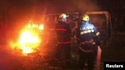 Firefighters try to extinguish a fire of a burning overturned police car in Luzhou, Sichuan province, October 17, 2012.