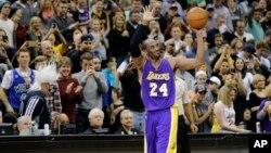 Pemain Los Angeles Lakers Kobe Bryant (24) mengangkat bola sambil menyapa penonton dalam pertandingan melawan Minnesota Timberwolves di Minneapolis (14/12). (AP/Ann Heisenfelt)