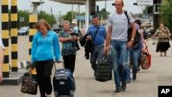 Dân chúng mang theo vật dụng tùy thân đi bộ sang trạm kiểm soát ở Izvaryne, vùng Luhansk ở miền đông Ukraine để vào lãnh thổ Nga, 26/6/14