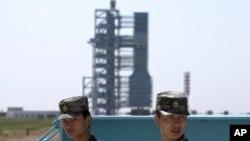 Ảnh tư liệu - Các binh sĩ Trung Quốc đứng gác gần tên lửa Long March 2F và tàu vũ trụ Thần Châu 10 tàu vũ trụ tại Trung tâm Phóng Vệ tinh Tửu Tuyền, tỉnh Cam Túc, tây bắc Trung Quốc.