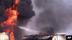 A Pakistani fire fighter tries to extinguish burning oil tankers after militants attacked a terminal in Quetta, Pakistan on Wednesday, Oct. 6, 2010.