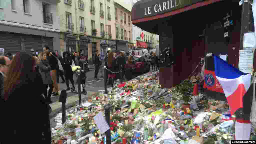 Mourners gather near Le Petit Cambodge and Le Carillon, which were the first restaurants hit in the multiple attacks across Paris Friday that left more than 120 people dead and hundreds wounded, Nov. 17, 2015.