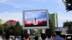 İnsanlar Pxenyanın dəmir yolu stansiyasının yerləşdiyi meydanda ballistik strateji raket sınağının televiziyada görüntülərini izləyir