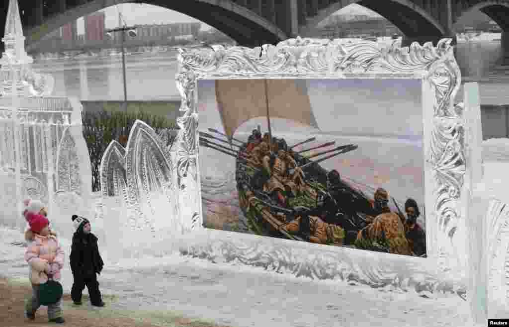 "Children walk past a reproduction of a creation by Russian classical painter Vasily Surikov, which is on display in an ice frame, before the opening of the 2nd International festival of snow and ice sculpture called ""The Magical Ice of the Siberia""  on the bank of the Yenisei River in Krasnoyarsk."