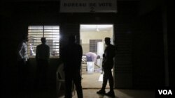 A guard and several bystanders are seen outside as votes are being counted at a polling station in Ouagadougou, Burkina Faso, November 29, 2015. (Photo - E. Iob/VOA)