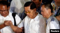 Mantan pemimpin senat Filipina Juan Ponce Enrile (kanan) dituntun para petugas saat menunggu ambulans menyusul penyerahan dirinya ke polisi atas tuduhan tindak pidana korupsi di markas besar Polisi Nasional FIlipina, Camp Crame, di Quezon city, Manila (4/7).
