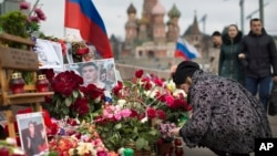 A woman lights a candle at the location where Russian opposition politician Boris Nemtsov was assassinated on February 27, 2015, near the Kremlin, in Moscow on April 7, 2015.