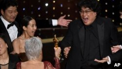 "Bong Joon Ho, right, reacts as he is presented with the award for best picture for ""Parasite"" from presenter Jane Fonda at the Oscars on Sunday, Feb. 9, 2020, at the Dolby Theatre in Los Angeles. Looking on from left are Kang-Ho Song and Kwak Sin Ae.(AP P"