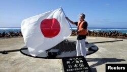 Thống đốc Tokyo Shintaro Ishihara vẫy cờ Nhật khi ông đến thăm đảo Okinotori island ngày 20/5/2005.