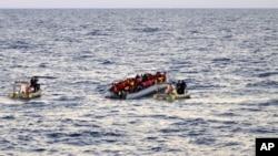 Bức ảnh do Hải quân Ý cung cấp cho thấy những đoàn cứu hộ đang tiến đến những di dân trên một chiếc thuyền cao su cách Tripoli, thủ đô Libya, khoảng 65km.