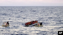 FILE - Photo provided by the Italian Navy shows rescue crews approaching migrants on a rubber boat some 40 miles (65 kilometers) from the Libyan capital, Tripoli.