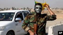 Un combatiente de las Fuerzas de Movilización Popular (UMP) de Irak monta guardia en Tuz Khormato, luego de ser evacuado por las fuerzas curdas.