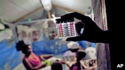 An employee of Haiti's Ministry of Health shows a device that measures the level of chlorine in the water consumed by earthquake survivors at a refugee camp in Port-au-Prince, 25 Oct 2010