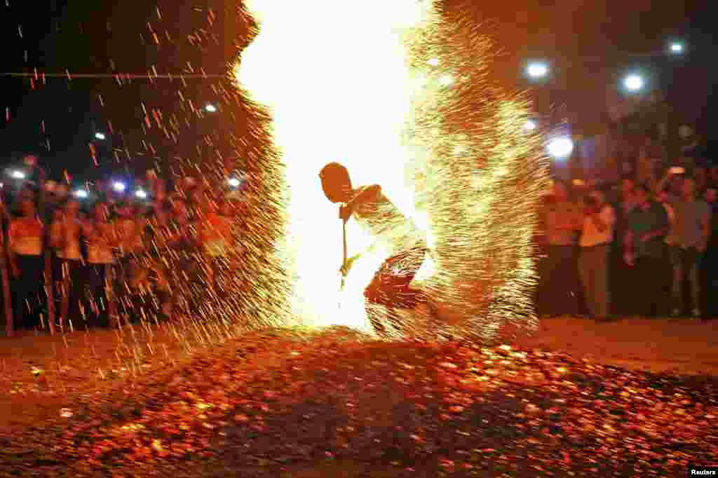 "A man runs through burning charcoal without shoes as he participates in a tradition called ""Lianhuo"", or ""fire walking"", in Pan'an county, Zhejiang province, China."