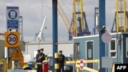 Policemen stand guard at an entrance to Tilbury Docks, east of London, Aug. 16, 2014.