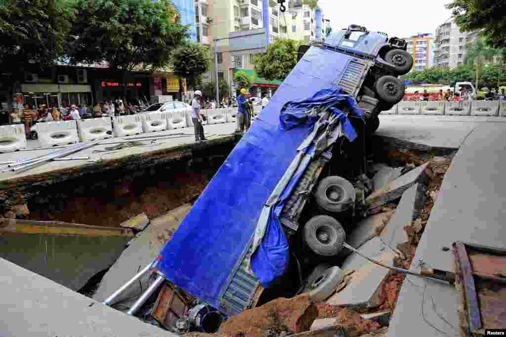 Công nhân đứng cạnh một chiếc xe tải bị mắc kẹt trong một cái hố lớn vì đất sụp trên đường phố ở Ngô Châu, khu tự trị dân tộc Tráng Quảng Tây, Trung Quốc.
