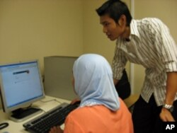 Nyein Kyaoo helps his students learn computer skills as well as the differences between Burmese and US society.