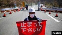 Nhân viên an ninh cầm cờ đỏ 'Xin dừng lại!' trước cổng vào thị trấn Tamura và Okuma ở Fukushima. Hơn 120.000 cư dân sống trong khu vực có bán kính 20km bao quanh Nhà máy điện hạt nhân Daiichi ở Fukushima vẫn chưa trở về lại nhà cửa của họ được vì mức phóng xạ ở đó vẫn còn cao.