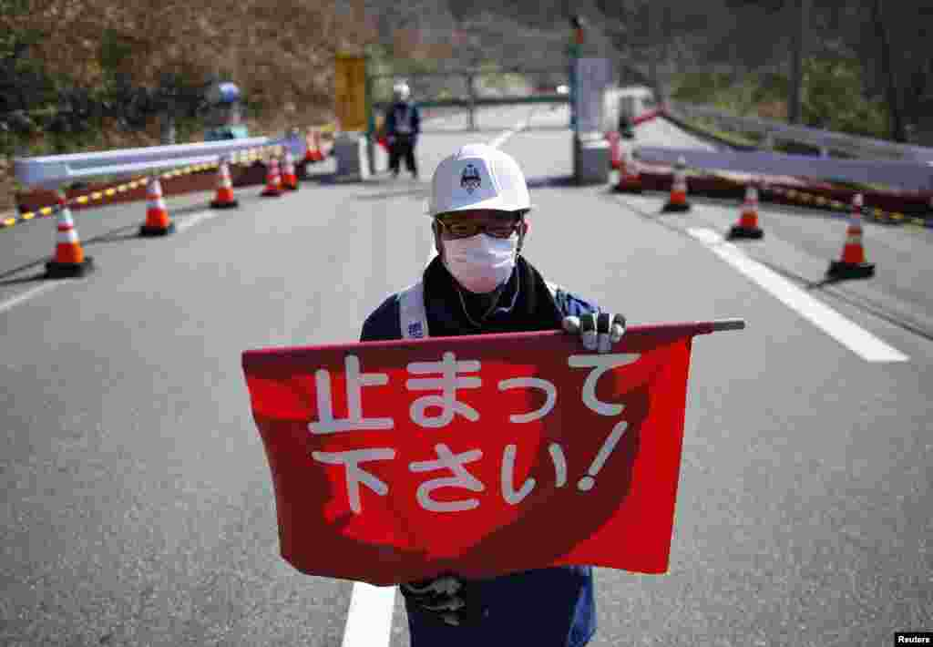"A security guard holds a flag that reads ""Please Stop!"", as he stands by a steel gate that marks the border between Tamura and Okuma town in Okuma town, Fukushima prefecture, April 1, 2014."