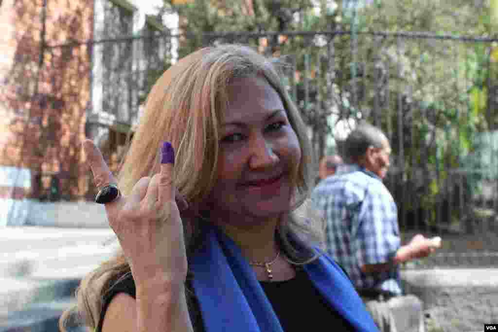 Una mujer muestra su dedo manchado de tinta indeleble luego de votar. [Foto: Iscar Blanco, VOA].