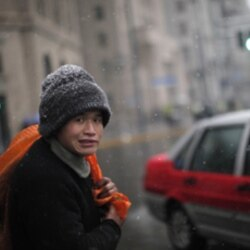 A man waits to cross a street during a snowstorm in Shanghai, China, on December 15