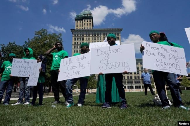 Un grupo de jóvenes sostiene carteles durante una vigilia en honor de las víctimas de un tiroteo masivo en Dayton, Ohio, el domingo 4 de agosto de 2019. REUTERS/Bryan Woolston.