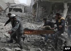 Members of the Syrian civil defence evacuate an injured civilian on a stretcher from an area hit by a reported regime air strike in the rebel-held town of Saqba, in the besieged Eastern Ghouta region on the outskirts of the capital Damascus.
