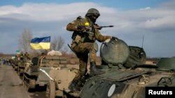 Konvoi pasukan bersenjata Ukraina menarik mundur kendaraan lapis baja, meriam dan senjata lainnya, dari kota Blagodatne, di wilayah Debaltseve, Ukraina Timur (27/2).