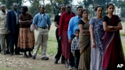 FILE - Members of a Kenyan family of Asian origin stand in line to cast their vote in Nairobi, Kenya, Dec. 27, 2007. On July 21, Kenya officially recognized Kenyan nationals of Asian descent as the country's 44th tribe. (AP Photo/Sayyid Azim)