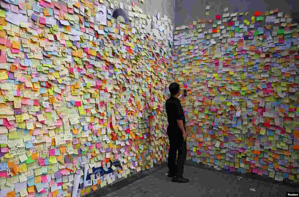 A man takes a picture on a wall full of messages left by pro-democracy protesters outside the government headquarters in Hong Kong. Hong Kong student protesters say they are determined to maintain their campaign for full democracy.
