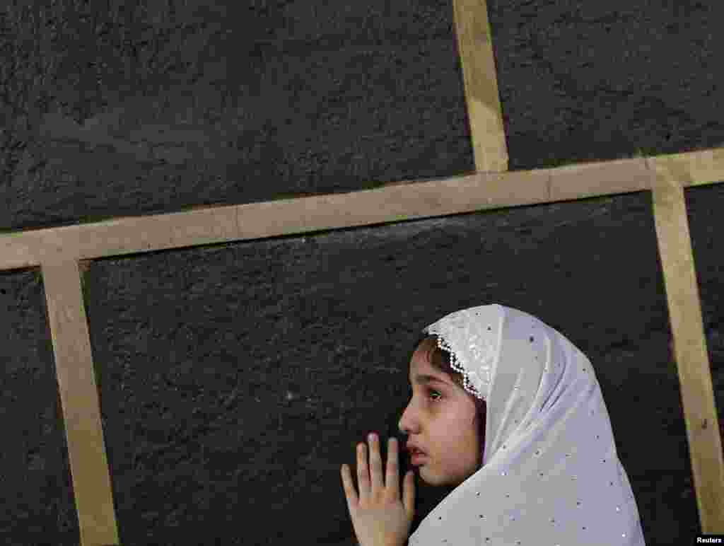A Muslim girl touches the holy Kaaba at the Grand Mosque on the first day of Eid al-Adha during the annual haj pilgrimage in Mecca, Saudi Arabia.