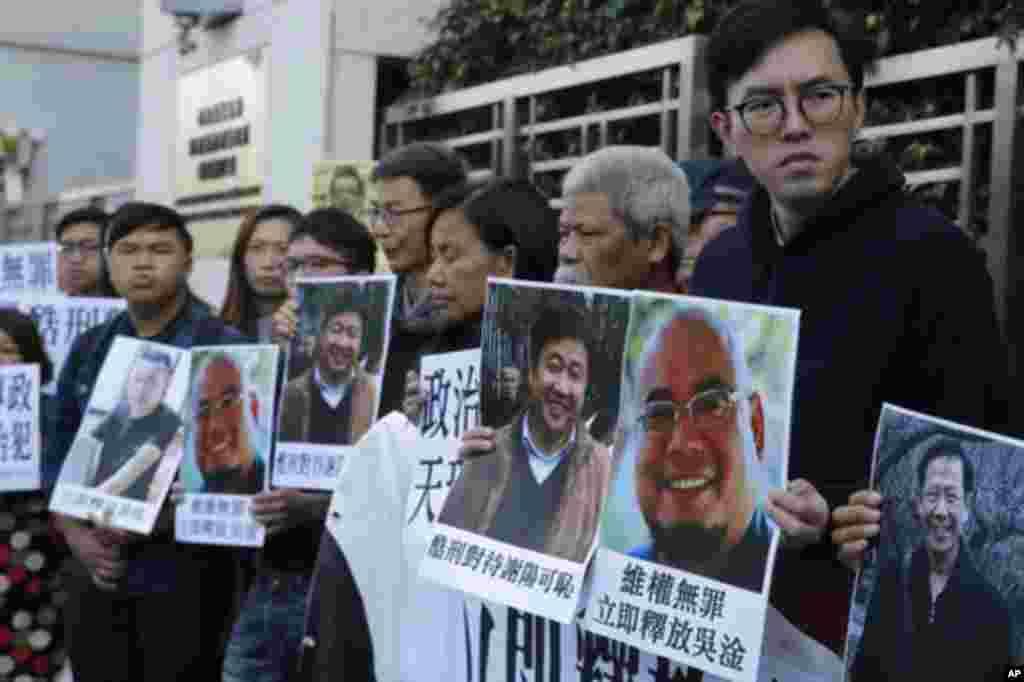"""香港民主派活跃分子手持吴淦和谢阳等维权人士的照片在中国中央政府驻港机构中联办外面声援吴淦和谢阳等人(2017年12月27日)。其中古思尧(右二)12月29号因涉嫌去年亵渎国旗被警方预约拘捕。在去年10月的一次抗议中,社民连成员古思尧抬着一个时钟示威道具,上面的中国国旗被倒置,寓意""""为共和国送终""""。香港媒体报道说,古思尧还被控7月在中联办外焚烧中国国旗。"""