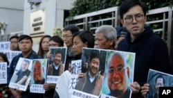 Pro-democracy activists hold pictures of Chinese activist Wu Gan, second right, and other activists outside the Chinese central government's liaison office in Hong Kong, Wednesday, Dec. 27, 2017.