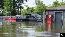 Two pickup trucks are seen surrounded by floodwater from the Mississippi River outside a garage in Memphis, Tennessee, May 8, 2011