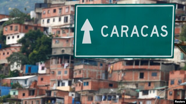 FILE - A road sign indicates the way to Caracas at Simon Bolivar international Airport in La Guaira, outside Caracas, Venezuela, July 10, 2013.
