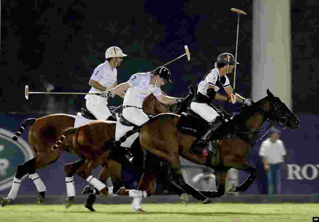 Britain's Prince Harry, center, plays in the Sentebale Polo Cup presented by the Royal Salute World Polo at the Ghantoot Polo Club in Abu Dhabi, United Arab Emirates.