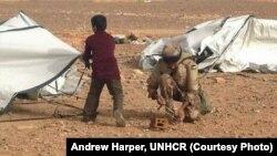 Một binh sĩ Jordan giúp một cậu bé Syria tị nạn dựng lều