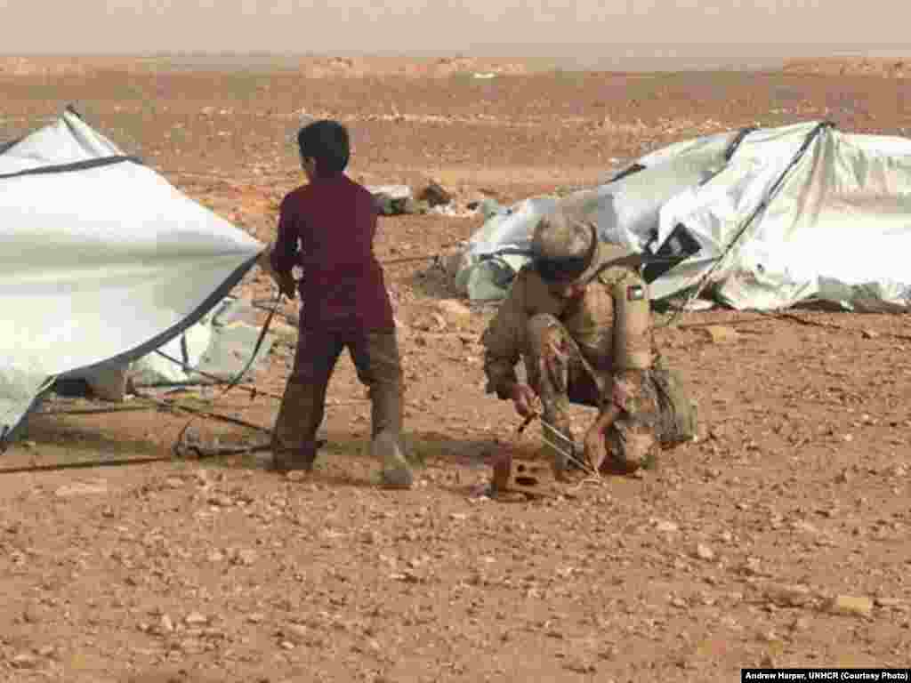 "A Jordanian soldier helping a young Syrian refugee put back up a tent blown down by the relentless wind. The UNHCR calls Jordan the ""model host."""