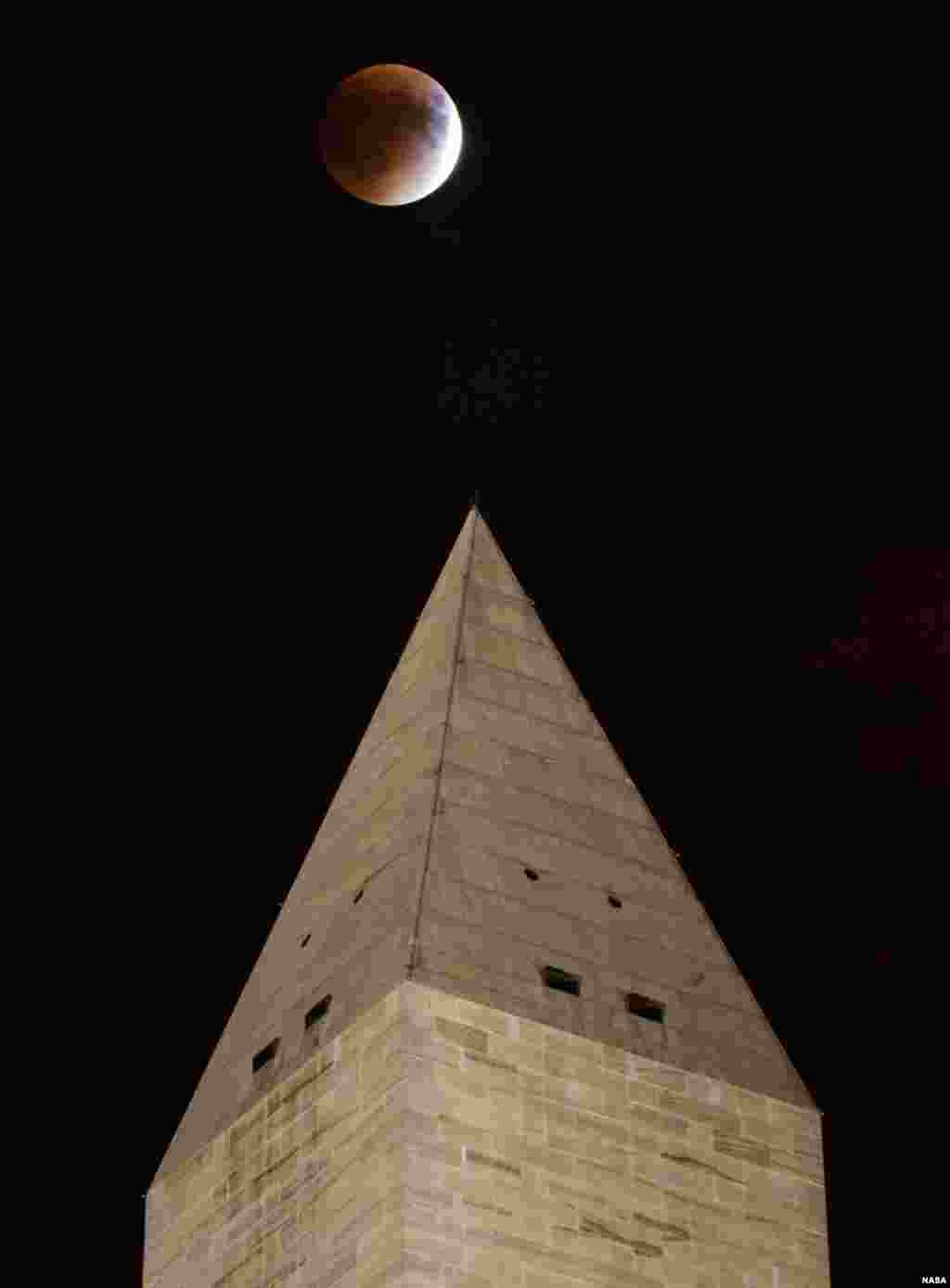 A perigee full moon, or supermoon, is seen behind the Washington Monument during a total lunar eclipse, Sept. 27, 2015, in Washington, D.C.  The combination of a supermoon and total lunar eclipse last occurred in 1982 and will not happen again until 2033. (NASA/Aubrey Gemignani)