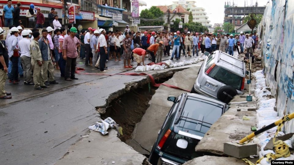 ​​Onlookers watch the cars sink in a hole by a construction site by Phnom Penh's Olympic Stadium after a heavy rain on Wednesday, June 8, 2016. (Courtesy of SBN)