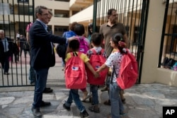 FILE - Refugee children enter a primary school in Athens on the first day of lessons under the new refugee schooling program, Oct. 10, 2016.