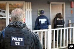 FILE - In this Feb. 9, 2017, photo provided by U.S. Immigration and Customs Enforcement, ICE agents are seen at a home in Atlanta.