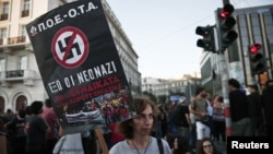 A protester holds a banner during an anti-fascist rally in Athens, Sept. 25, 2013.