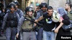 An Israeli policeman prevents a Palestinian man from entering the compound which houses al-Aqsa mosque, known by Muslims as the Noble Sanctuary and by Jews as the Temple Mount, in Jerusalem's Old City Sept. 28, 2015.