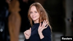 FILE - British designer Stella McCartney appears at the end of her Fall/Winter 2017-2018 women's ready-to-wear collection show during Paris Fashion Week, in Paris, March 6, 2017. Last year, McCartney became the first designer to sign up with the Make Fashion Circular initiative, which aims to eliminate waste and pollution and ensure products and materials are reused.