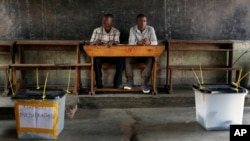 Election observers sit in an empty polling station for the presidential elections in Bujumbura, Burundi, July 21, 2015.